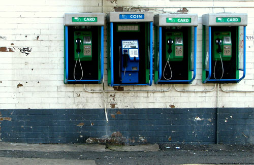 One coin operated phone next to three card operated call boxes